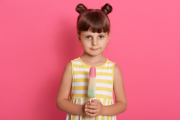 Shy charming girl with sorbet in hands, dresses summer outfit, has two knots, standing isolated on pink