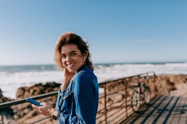 Застенчивая очаровательная женщина с вьющимися волосами в джинсовой рубашке слушает музыку