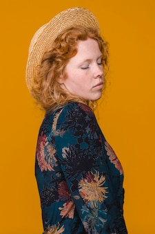 Shy curly redheaded female in studio with bright background