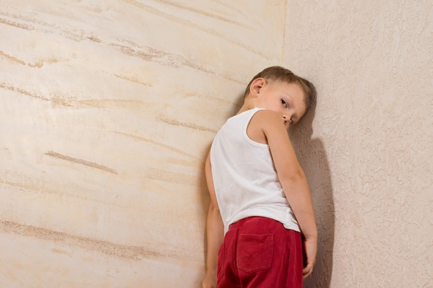 Shy cute little boy isolated on wooden walls.