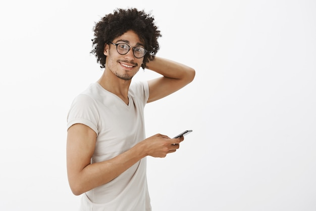 Shy cute man in glasses using mobile phone and smiling awkward