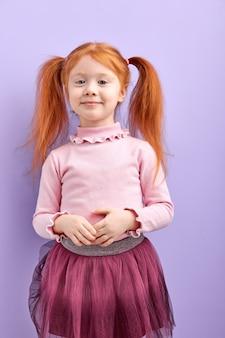 Застенчивая прилежная рыжая девочка с двумя хвостиками позирует, улыбается, невероятная девушка в изолированной юбке
