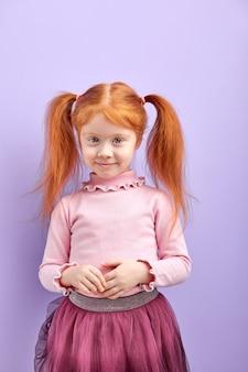 紫にポーズをとる2つのポニーの尾を持つ恥ずかしがり屋の勤勉な赤毛の子供の女の子