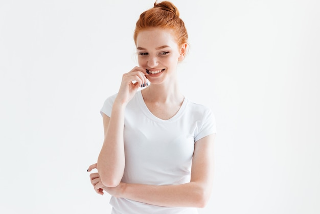 Shy ginger woman in t-shirt looking down