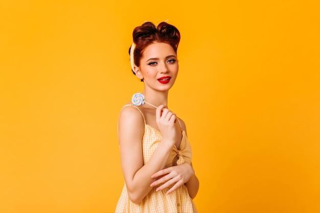 ロリポップを保持している恥ずかしがり屋の生姜の若い女性。黄色いスペースにキャンディーを持っている魅力的なピンナップガールのスタジオショット。