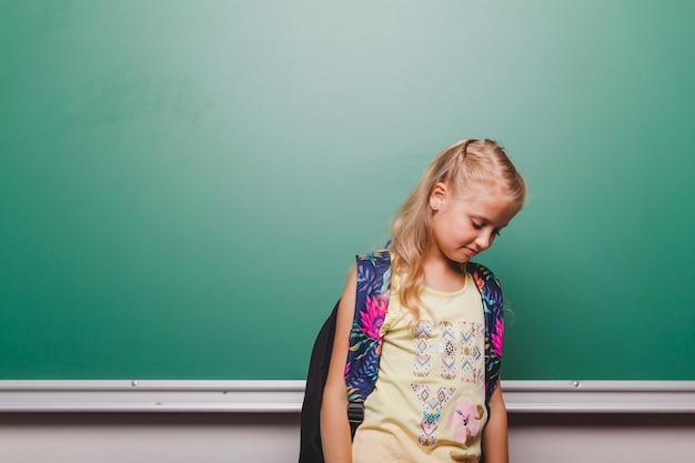Shy girl at blackboard