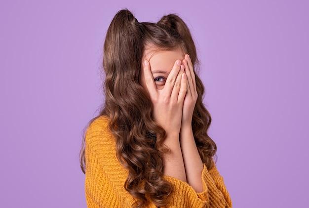 Застенчивая девушка с длинными волнистыми хвостиками, пряча лицо и выглядывающая сквозь пальцы