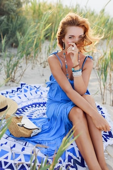 Shy girl with perfect tan skin posing on sunny beach in trendy blue dress, sitting on sand.