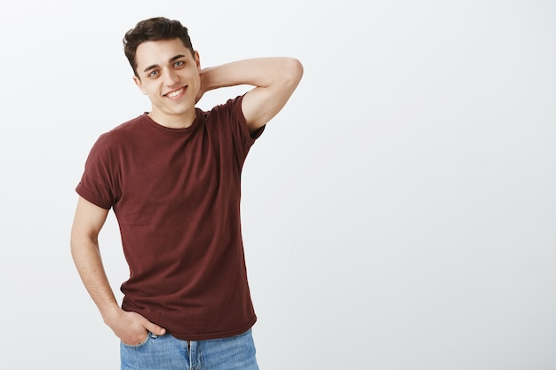 Застенчивый красивый мужской парень в красной футболке