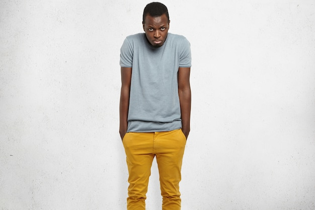 Shy handsome young african american man feeling embarassed or uncomfortable, shrugging shoulders, keeping hands in pockets of his mustard jeans, looking with unhappy expression, pouting