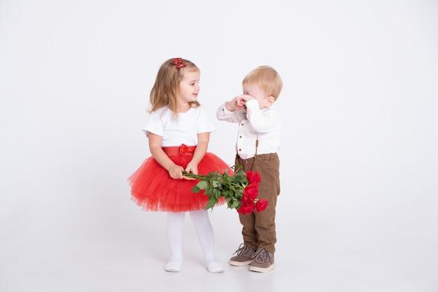 Застенчивый маленький мальчик дарит букет роз девочке малыша в день святого валентина на белом фоне.