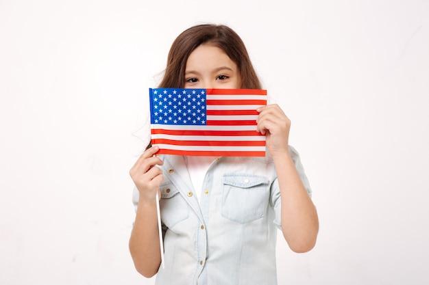 Застенчивый маленький очаровательный ребенок демонстрирует американский флаг, выражая положительные эмоции и стоя у белой стены
