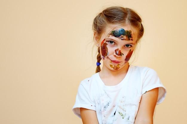 カメラを見て塗られた顔と白いtシャツの恥ずかしがり屋の少女
