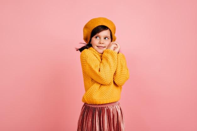 분홍색 벽에 포즈 수줍은 어린 소녀. 노란색 복장에 귀여운 아이.