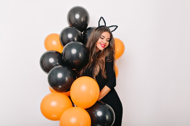 Shy long-haired woman posing with colorful halloween balloons