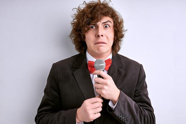 白い壁に隔離されたマイクと恥ずかしがり屋の男性の演説者。巻き毛の男は、人々や聴衆の群衆のためにスピーチをすることを恐れています