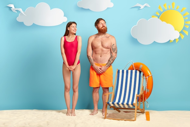 Shy pleased female and male tourist, look gladfully aside, keep hands together, woman wears red bikini
