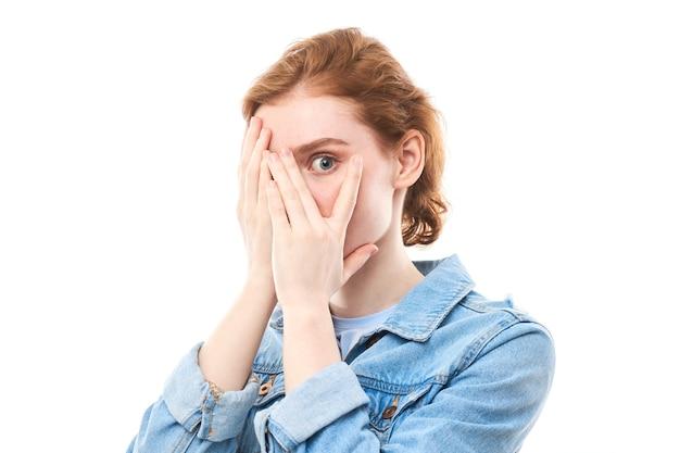 恥ずかしがり屋の赤毛の女の子が手で顔を覆い、指でカメラをのぞきます。隠れている、怖い、または恥ずかしい白い孤立した背景の若い女性。体の言語