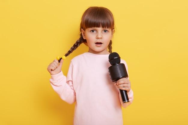 마이크에서 노래하는 땋은 머리를 가진 수줍은 작은 여자 아이, 옅은 분홍색 캐주얼 셔츠를 입고 공연하는 귀여운 유럽 소녀는 현대 대중 노래, 매력적인 예술가를 노래합니다.