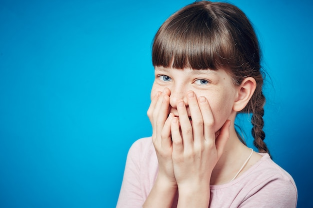 Shy smiling embarrassed girl covering mouth with hands. young cute child emotional portrait