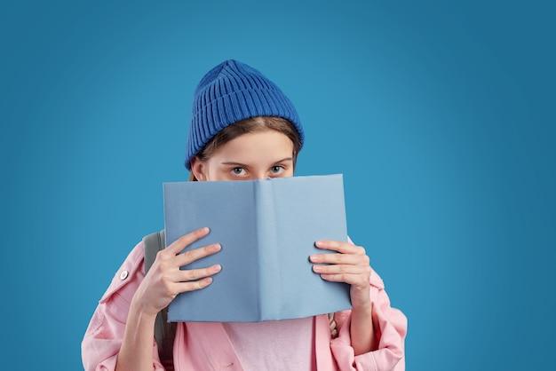 Застенчивая девочка-подросток в синей шапке и розовой джинсовой куртке выглядывает из раскрытой книги у ее лица, стоя перед камерой