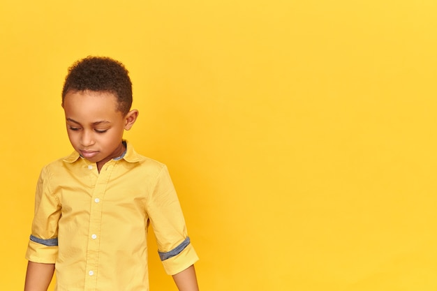 Shy timid little african boy being embarrassed looking down feeling ashamed of bad behavior isolated on blank yellow wall