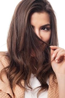 Shy woman hiding behind her hair
