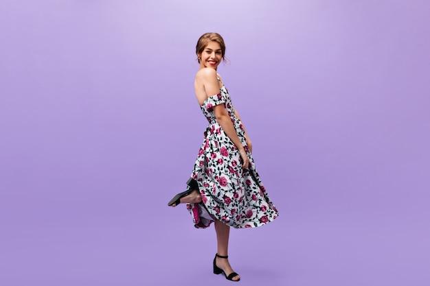 유행 드레스에 수줍은 여자는 보라색 배경에 포즈. 카메라에 웃 고 화려한 현대 옷에 아름 다운 세련 된 아가씨.
