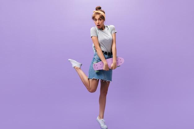 Застенчивая женщина поднимает ногу и держит лонгборд на фиолетовом фоне. симпатичная дама в летнем стильном наряде позирует на изолированном фоне.