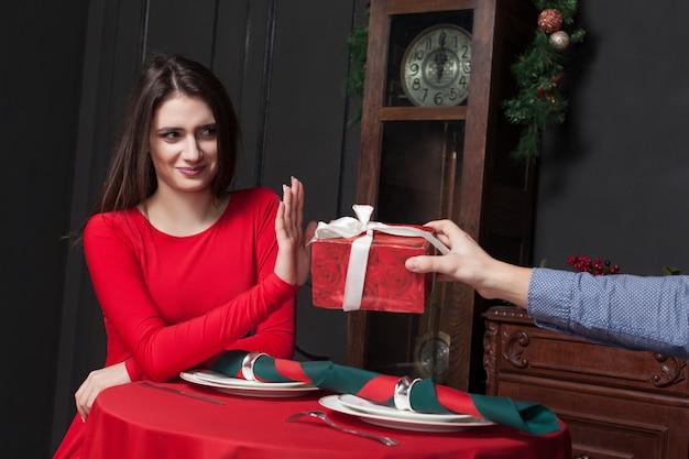 Застенчивая женщина отказывается от подарка в ресторане