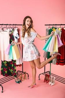 Застенчивая женщина, стоящая в магазине возле вешалки и держащая разноцветные хозяйственные сумки, изолированные на розовом