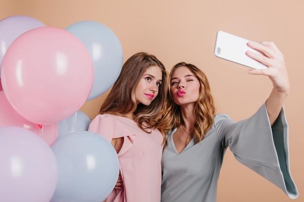 パーティー風船でポーズをとるピンクの口紅を持つ恥ずかしがり屋の女性