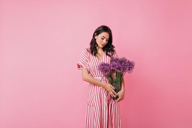 巻き毛の黒い髪の恥ずかしがり屋の少女は見下ろし、花の壮大な花束を賞賛します。