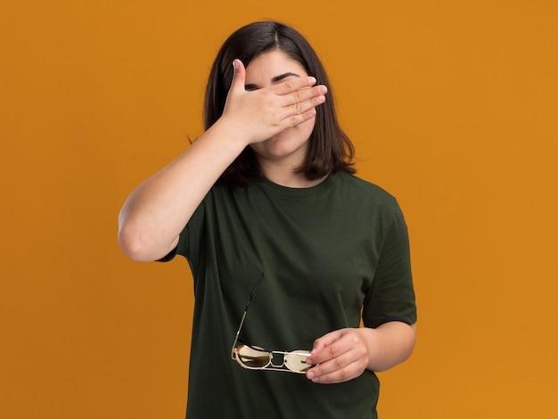 Timida giovane ragazza abbastanza caucasica tiene la mano davanti al viso e tiene gli occhiali da sole isolati sulla parete arancione con lo spazio della copia