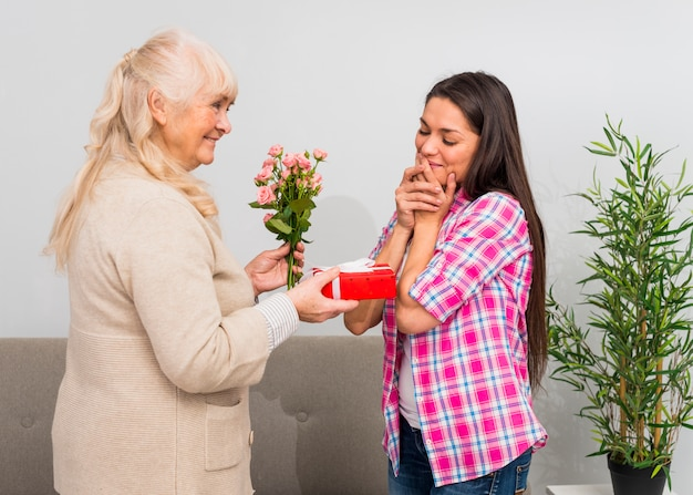 Shy young woman looking at smiling mother holding roses bouquet and gift box