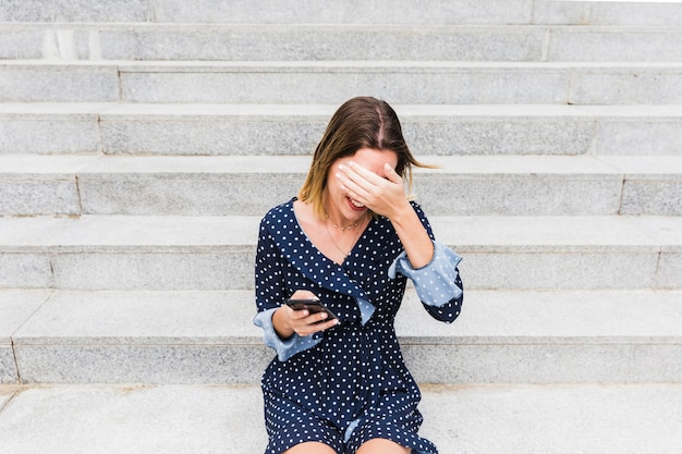 Shy young woman sitting on staircase holding smartphone