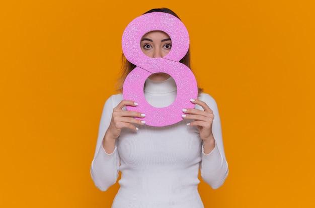 Timida giovane donna in dolcevita bianco azienda numero otto realizzato in cartone lookingat anteriore per celebrare la giornata internazionale della donna in piedi sopra la parete arancione
