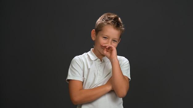 Застенчиво смеющийся мальчик закрывает лицо рукой, глядя вперед в белой рубашке-поло и черных штанах, изолированных на черной стене