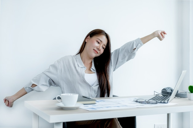 Sian businesswoman feeling pain and stretch herself after working hard on laptop office syndrome
