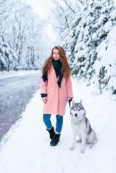Сибирский хаски сидит рядом с молодой женщиной