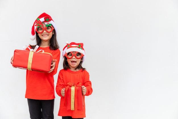 Брат и сестра азиатские девушки в красной шляпе санты с подарочными коробками на белом фоне.