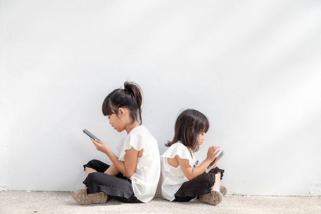 형제 자매들은 흰색 배경에서 스마트폰을 사용하는 것을 즐깁니다. 통신 기술과 사람들의 개념