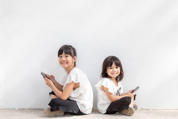 형제 자매는 흰색 배경에서 스마트폰을 사용하는 것을 즐깁니다. 통신 기술의 개념