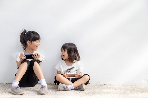 兄弟の女の子は白い背景でスマートフォンを使用して楽しむ通信技術の概念