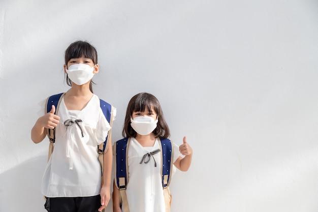 コロナウイルスの発生を阻止するためにマスクを身に着けている兄弟の少女