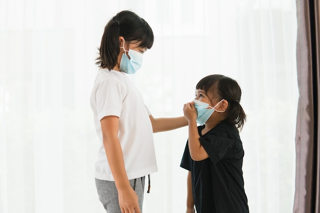 집에서 코로나 바이러스 발병을 막기 위해 마스크를 쓴 형제 자매