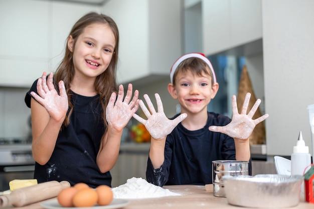 兄弟は、クリスマスの帽子をかぶった男の子で、台所で料理をして浮気しています。幸せな子供のアイデア