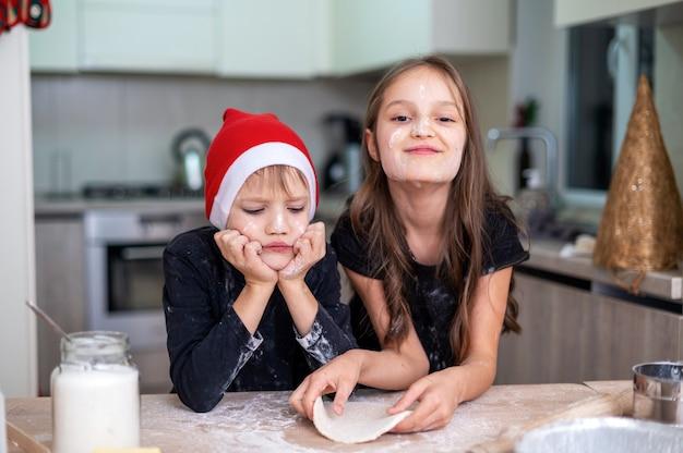 兄弟は台所で料理とポーズをとっています、クリスマスの帽子をかぶった男の子、女の子は笑っています。小麦粉の顔。幸せな子供のアイデア