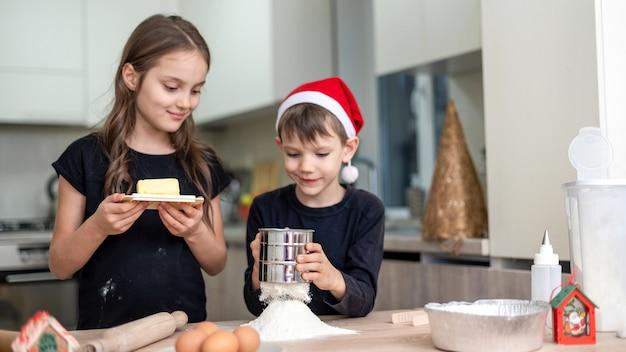 兄弟は台所で料理をしている、男の子はクリスマスの帽子をかぶっている。幸せな子供のアイデア