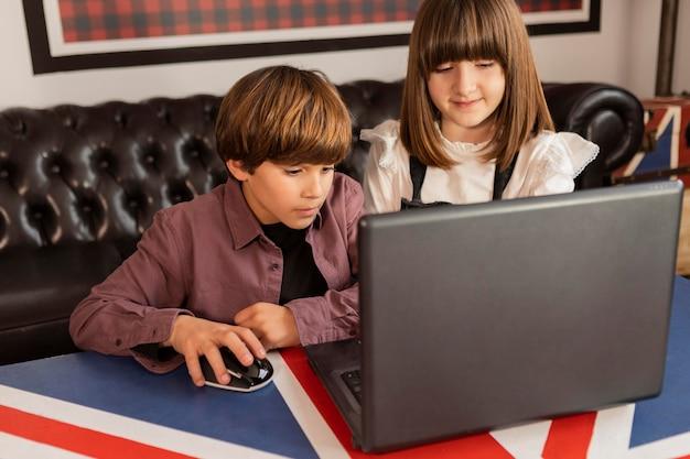 집에서 노트북을 사용하는 형제 자매